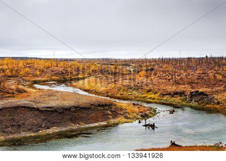 The river flows through the polar tundra. Norilsk Taimyr Peninsula area. Deep autumn Arctic tundra.