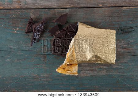 Dark chocolate wrapped in gold foil on old vintage table stock photo