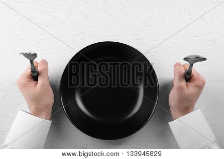 Man holding fork and spoon with empty plate. Hunger concept