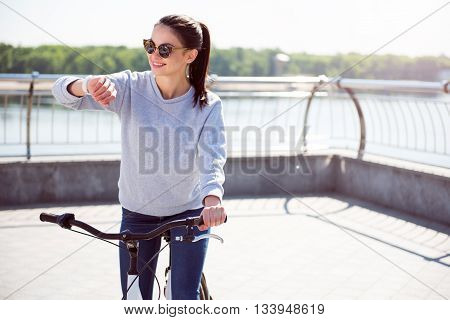 Where is he. Pleasant young woman with sunglasses looking at her watch while standing with a bicycle