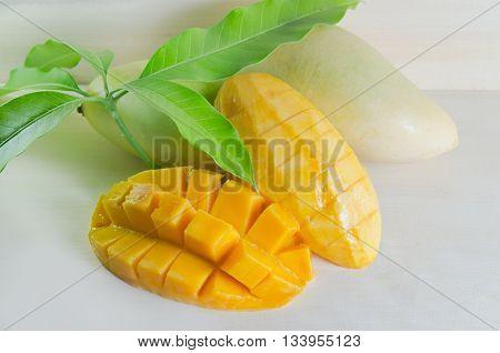 Mango ripe with nicely cut pieces and leaf on wooden board (Other names of mango are horse mango Mangifera foetida Anacardiaceae Mangifera M. indica)