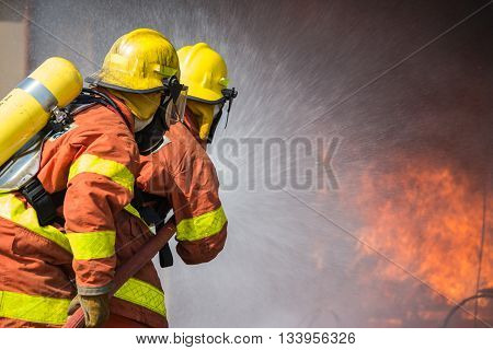 2 firefighters spraying water fire fighting operation