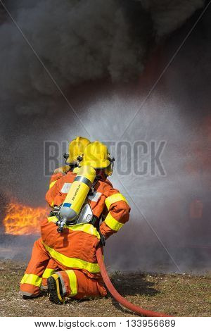 2 firemen spraying water in fire fighting with fire and dark smoke background