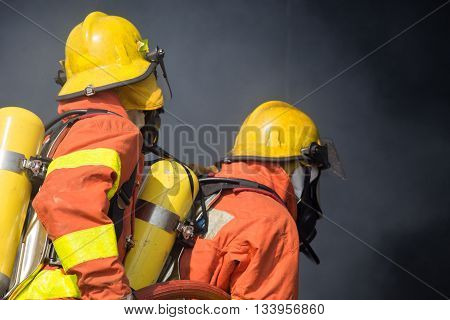 2 firefighters in operation and dark smoke background