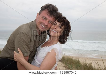 Attractive Couple Cuddling At The Beach Smiling