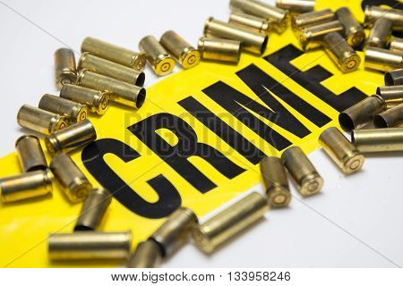 word crime on yellow tape with brass bullet case on white background