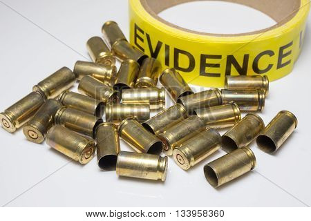 evidence tape with brass bullet cases on white background