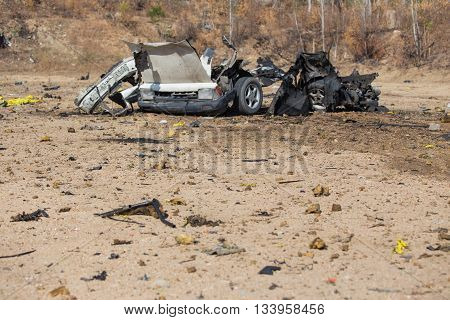 car wrecked and parts from car bomb in crime scene