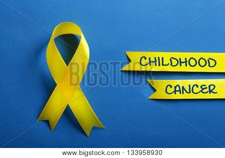 Yellow ribbon and text Childhood Cancer on blue background