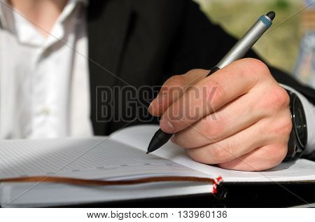 Left handed businessman is writing something in a notebook