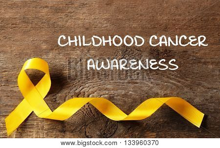 Yellow ribbon and text Childhood Cancer Awareness on wooden background