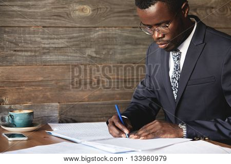 Serious Black Corporate Worker In Formal Suit And Spectacles Signing A Lucrative Contract With Conce