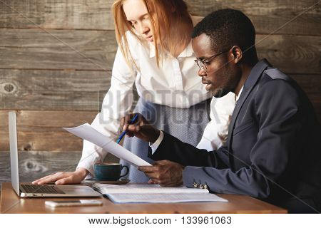 Colleagues Discussing Documents Sitting In The Office. African Executive Officer Holding Papers, Exp