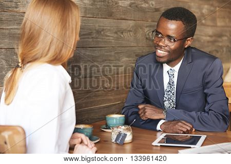 Portrait Of Two Corporate Workers Of Different Races: Smiling African Man In Formal Wear Discussing