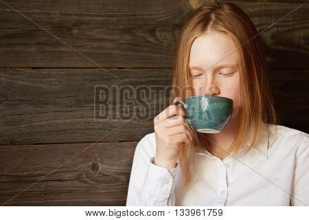 Young Beautiful Lady Drinking Tasty Coffee On Wooden Background. Blond Caucasian Girl In Office Dres