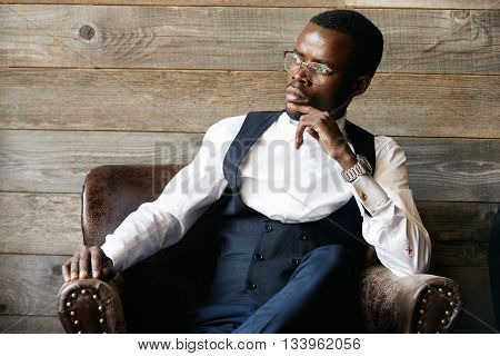 Successful Young Dark-skinned Entrepreneur In Formal Clothing, Sitting In Leather Armchair Against W