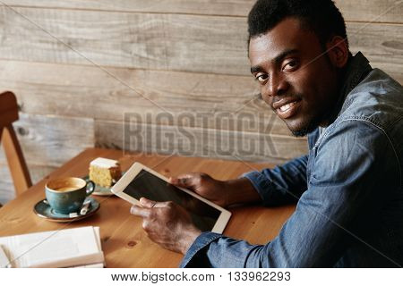 Portrait Of Handsome Black Student In Denim Wear, Looking At The Camera With Happy Expression While