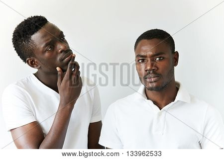 Two African Men In Casual Wear Posing Isolated Against White Studio Wall. Young Black Guy Looking At