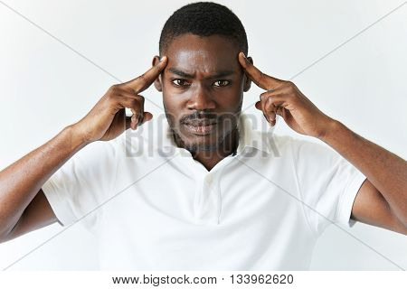 Portrait Of Sad Unhappy African Man Having Bad Headache, Looking At The Camera With Painful Expressi