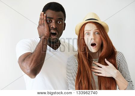Surprised And Horrified Couple Looking At Camera With Eyes Wide-opened. Afro American Man Slapping F