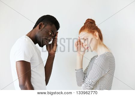 Sideways Portrait Of Couple In Disappointed Pose In White Studio. Caucasian Girl Resting Her Head On