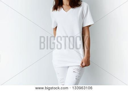 Cropped Isolated Shot Of Young Female Model In Trendy Ripped Denim Pants Stretching Her Blank T-shir
