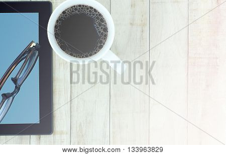 Tablet eyeglasses and a cup of coffee on wood pattern background. Business communication concept. Vintage tone color.
