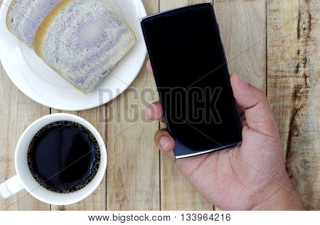 A cup of coffee bread on white plate smartphone in hand on wood background. Hand holding smartphone with breakfast set on the wooden table. morning working concept.