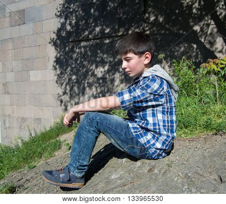 Teenage boy sits on a clif in a city park area