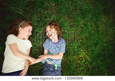 Two cheerful children lie on a green grass. The boy and the girl lie having joined hands and laugh. They look at each other.