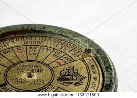 Close up of green marble and brass perpetual calendar on white background with copy space