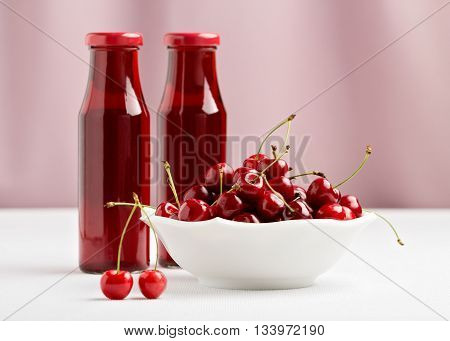 Cherries in a bowl and two bottles of cherry juice. Selective focus.