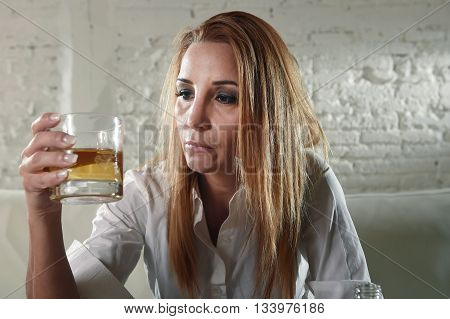 blond sad and wasted alcoholic drunk woman sitting at home sofa couch drinking scotch whiskey holding glass depressed lonely and suffering hangover in alcoholism and alcohol abuse
