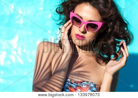 Colorful portrait of young attractive woman wearing sunglasses. Summer beauty skin care concept