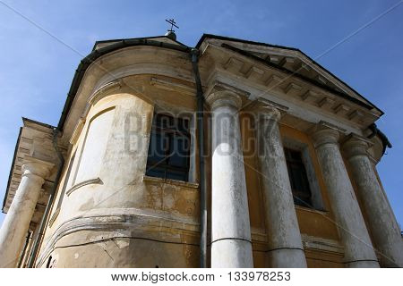 old orthodox church in classical style with classical white portico and yellow shabby walls and cross on top