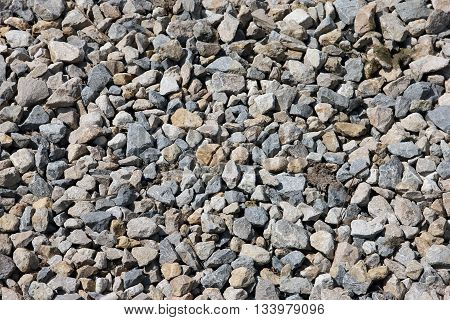 texture of grey color of the crushed granite and limestone coarse gravel foreground closeup