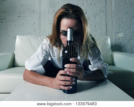 blond sad and wasted alcoholic woman sitting at home sofa couch drinking red wine holding bottle sleeping drunk looking depressed lonely and suffering hangover in alcoholism and alcohol abuse