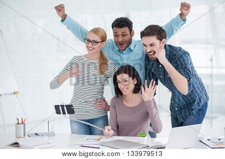 Positivity in work place. Group of businesspeople giving thumbs up to smartphone making selfie