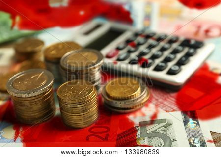 Grey calculator, banknotes and coins with bloodstains