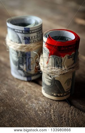 Dollars roll with bloodstains on wooden background