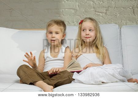 two Smiling children twings read a story