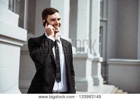 Glad to hear you. Cheerful delighted handsome man smiling and talking on cell phone while expressing gladness