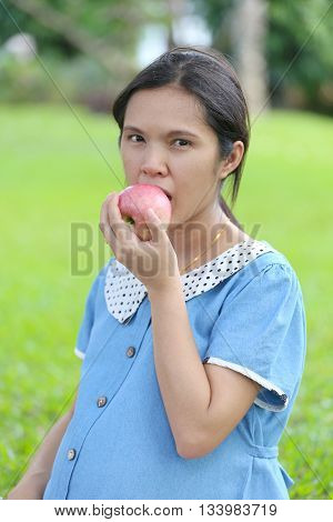 Asian pregnant women using hand catch apple up eating in the public park.
