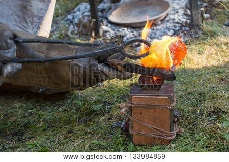 smith pouring liquid bronze into model - closeup
