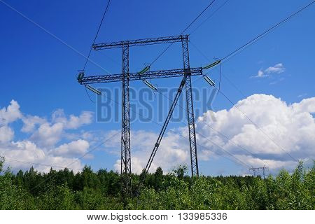 Reliance power line with cables on background of blue sky with clouds.