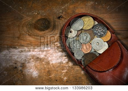 Macro photography of a brown leather coin purse with old and vintage coins. On a wooden table