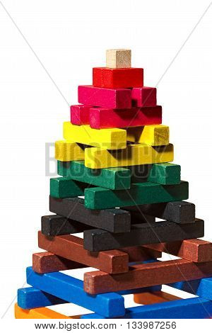 Close up of a pyramid made with colorful pieces of wood. Toy for learn the creativity and dexterity. Isolated on white