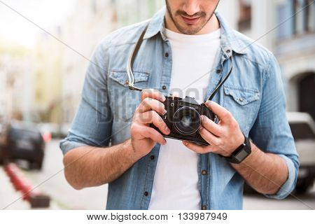 Time for hobby. Pleasant handsome man holding photo camera while resting outdoor poster