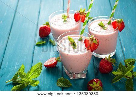 Milkshake. Milkshake with fresh strawberries in a glass jar on blue table. dairy drink.