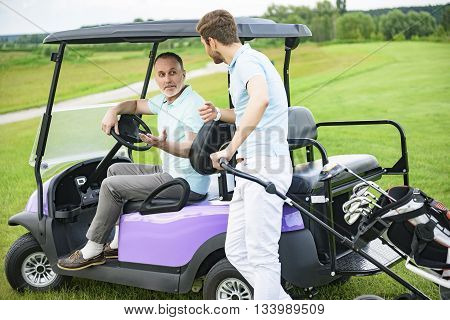 Having great day out on green. Son standing near golf cars and discussing upcoming game with his father, siting on buggy